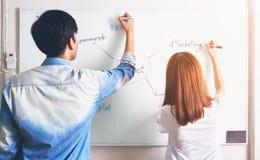 De mannen en de vrouw schrijven een plan op een witte raad Om aan het team voor te stellen Stock Afbeelding