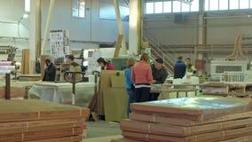 De mannen en de vrouwen, arbeiders bespreken het proces om in een grote workshop te werken Het proces om houten deuren te maken stock videobeelden