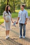 De mannen van het familiepaar en een jong zwanger vrouw het lopen stuk speelgoed van de holdingsteddybeer in het park stock afbeeldingen