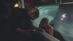 De mannequin die van de vrouwenfotograaf samen foto na zitting onderwater in zwembad kijken stock footage