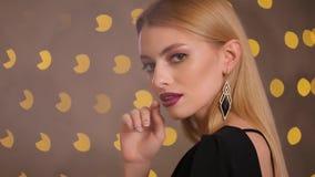 De mannequin zet op dure oorring op haar oor, langzame motie stock video