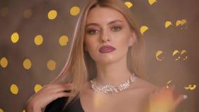De mannequin zet op halsband in gele lichten bokeh, langzame motie stock videobeelden