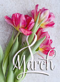 8 de março, cartão do dia das mulheres internacionais Figura branca oito e um ramalhete de três tulipas vermelhas Foto de Stock Royalty Free