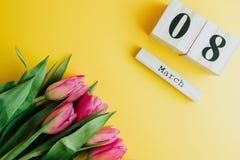 8 de março conceito feliz do dia do ` s das mulheres Com o calendário de bloco de madeira e as tulipas cor-de-rosa no fundo amare Fotografia de Stock Royalty Free
