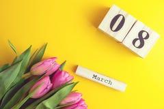 8 de março conceito feliz do dia do ` s das mulheres Com o calendário de bloco de madeira e as tulipas cor-de-rosa no fundo amare Fotografia de Stock