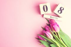 8 de março conceito feliz do dia do ` s das mulheres Com o calendário de bloco de madeira e as tulipas cor-de-rosa no fundo cor-d Imagem de Stock
