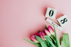 8 de março conceito feliz do dia do ` s das mulheres Com o calendário de bloco de madeira e as tulipas cor-de-rosa no fundo cor-d Fotografia de Stock