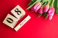 8 de março conceito feliz do dia do ` s das mulheres Com o calendário de bloco de madeira e as tulipas cor-de-rosa no fundo verme Imagens de Stock Royalty Free
