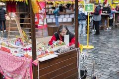 25 DE MARÇO DE 2016: Uma senhora mais idosa que vende ovos decorados em sua cabine de madeira nos mercados da Páscoa no quadrado  Imagens de Stock Royalty Free
