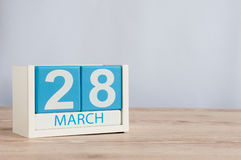 28 de março Dia 28 do mês, calendário de madeira da cor no fundo da tabela Tempo de mola, espaço vazio para o texto Imagem de Stock
