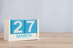 27 de março Dia 27 do mês, calendário de madeira da cor no fundo da tabela Tempo de mola, espaço vazio para o texto Teatro do mun Fotos de Stock