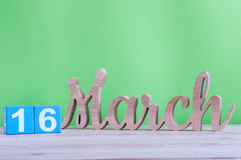 16 de março Dia 16 do mês, calendário de madeira diário na tabela e fundo verde Dia de mola, espaço vazio para o texto Fotografia de Stock Royalty Free