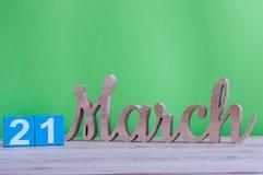 21 de março dia 21 do mês, calendário de madeira diário na tabela e fundo verde Tempo de mola, espaço vazio para o texto Imagem de Stock