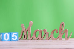 5 de março Dia 5 do mês, calendário de madeira diário na tabela e fundo verde Tempo de mola, espaço vazio para o texto Fotos de Stock Royalty Free