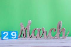 29 de março Dia 29 do mês, calendário de madeira diário na tabela e fundo verde Tempo de mola, espaço vazio para o texto Imagens de Stock Royalty Free