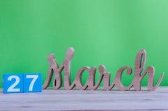 27 de março Dia 27 do mês, calendário de madeira diário na tabela e fundo verde Tempo de mola, espaço vazio para o texto Imagens de Stock Royalty Free