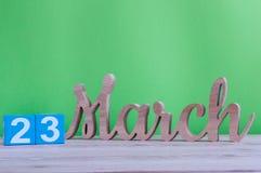 23 de março Dia 23 do mês, calendário de madeira diário na tabela e fundo verde Tempo de mola, espaço vazio para o texto Fotografia de Stock