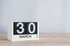 30 de março Dia 30 do mês, calendário de madeira no fundo claro Tempo de mola, espaço vazio para o texto Imagem de Stock Royalty Free