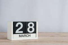 28 de março Dia 28 do mês, calendário de madeira no fundo claro Tempo de mola, espaço vazio para o texto Fotos de Stock Royalty Free