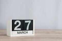 27 de março Dia 27 do mês, calendário de madeira no fundo claro Tempo de mola, espaço vazio para o texto Dias do teatro do mundo Foto de Stock