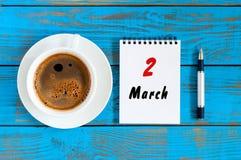 2 de março Dia 2 do mês, calendário escrito e copo de café da manhã no fundo de madeira azul Tempo de mola, vista superior Imagem de Stock Royalty Free