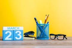 23 de março Dia 23 do mês, calendário na luz - fundo amarelo, local de trabalho com suplies do escritório Tempo de mola, vazio Fotos de Stock