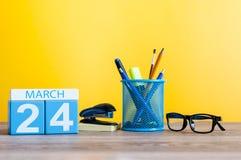 24 de março Dia 24 do mês, calendário na luz - fundo amarelo, local de trabalho com suplies do escritório Tempo de mola, vazio Fotografia de Stock Royalty Free