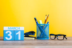31 de março dia 31 do mês, calendário na luz - fundo amarelo, local de trabalho com suplies do escritório Tempo de mola, vazio Fotos de Stock