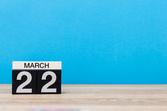 22 de março Dia 22 do mês, calendário na tabela com fundo azul Tempo de mola, espaço vazio para o texto Imagem de Stock