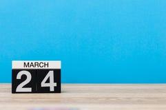 24 de março Dia 24 do mês, calendário na tabela com fundo azul Tempo de mola, espaço vazio para o texto Imagens de Stock