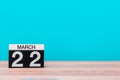 22 de março Dia 22 do mês, calendário na tabela com fundo de turquesa Tempo de mola, espaço vazio para o texto Fotografia de Stock