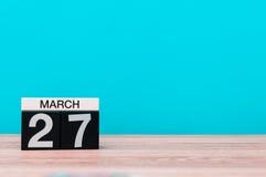 27 de março Dia 27 do mês, calendário na tabela com fundo de turquesa Tempo de mola, espaço vazio para o texto mundo Foto de Stock Royalty Free