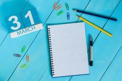 31 de março dia 31 do mês, calendário no fundo de madeira azul da tabela com bloco de notas Tempo de mola, espaço vazio para o te Fotos de Stock