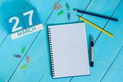 27 de março Dia 27 do mês, calendário no fundo de madeira azul da tabela com bloco de notas Tempo de mola, espaço vazio para o te Fotos de Stock Royalty Free