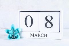 8 de março, dia internacional do ` s das mulheres Calendário perpétuo de madeira e flor de papel azul Imagem de Stock Royalty Free