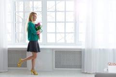 8 de março, a mulher bonita nova com as tulipas na camiseta verde sunlight Imagem de Stock Royalty Free