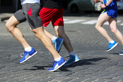 De marathonnen van de atletenlooppas op de bestrating Stock Foto's