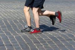 De marathonnen van de atletenlooppas op de bestrating Stock Afbeelding