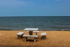 De marmortabellen och stolarna på stranden royaltyfri foto