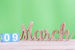 9 de marzo Día 9 de mes, calendario de madera diario en la tabla y fondo verde Día de primavera, espacio vacío para el texto Fotografía de archivo libre de regalías