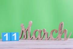 11 de marzo Día 11 de mes, calendario de madera diario en la tabla y fondo verde Día de primavera, espacio vacío para el texto Fotografía de archivo libre de regalías