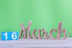 16 de marzo Día 16 de mes, calendario de madera diario en la tabla y fondo verde Día de primavera, espacio vacío para el texto Fotografía de archivo libre de regalías