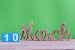 10 de marzo Día 10 de mes, calendario de madera diario en la tabla y fondo verde Día de primavera, espacio vacío para el texto Fotos de archivo