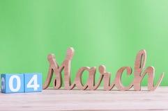 4 de marzo Día 4 de mes, calendario de madera diario en la tabla y fondo verde Tiempo de primavera, espacio vacío para el texto Imagen de archivo