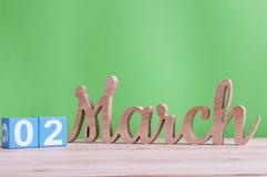 2 de marzo Día 2 de mes, calendario de madera diario en la tabla y fondo verde Tiempo de primavera, espacio vacío para el texto Fotos de archivo libres de regalías
