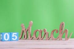 5 de marzo Día 5 de mes, calendario de madera diario en la tabla y fondo verde Tiempo de primavera, espacio vacío para el texto Fotos de archivo libres de regalías
