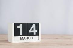 14 de marzo Día 14 del mes, calendario de madera en fondo ligero El tiempo de primavera… subió las hojas, fondo natural La Common Foto de archivo