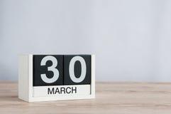 30 de marzo Día 30 del mes, calendario de madera en fondo ligero Tiempo de primavera, espacio vacío para el texto Imagen de archivo libre de regalías