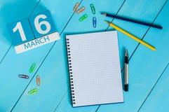 16 de marzo Día 16 del mes, calendario en fondo de madera azul de la tabla con la libreta Tiempo de primavera, espacio vacío para Imagenes de archivo