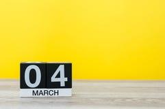 4 de marzo Día 4 del mes, calendario en la tabla con el fondo amarillo Tiempo de primavera, espacio vacío para el texto Foto de archivo
